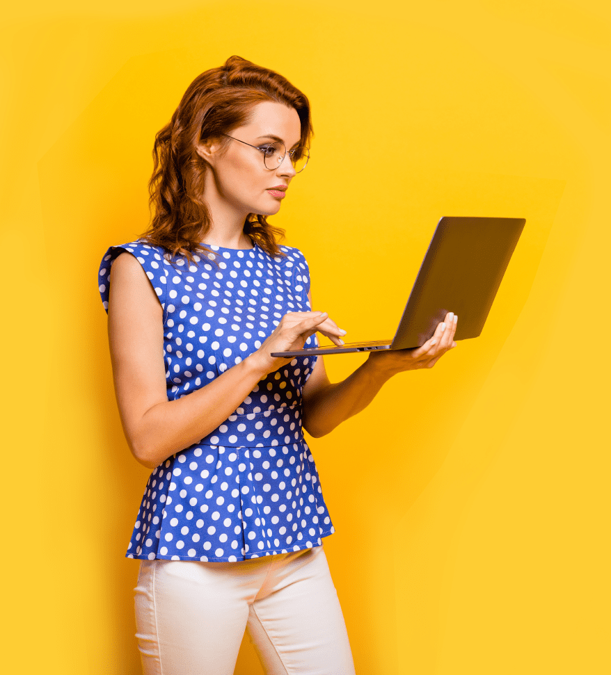 Woman in a blue and white polka dot top against a yellow background holding and looking at an open laptop screen