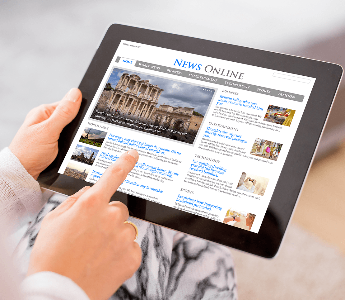 Close up of hand holding a tablet displaying a news site