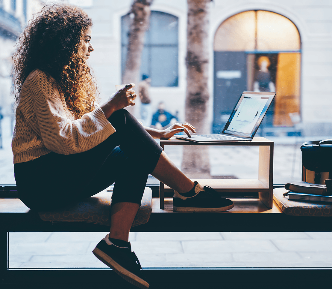 Woman sitting on a bench in a coffee shop working on a laptop